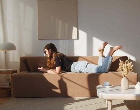 Kvinde ligger i sofa med computer