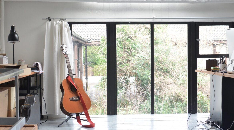Stue med guitar og stort vindue